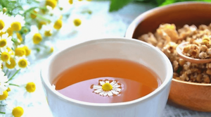 Chamomile tea in a white cup, with a blossom chamomile floating in the center on the cup