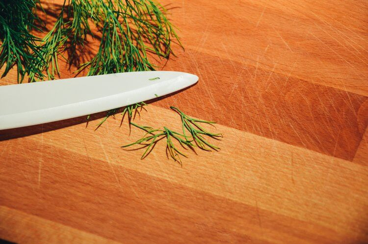 Dill weed chopped by a knife on wooden cutting board
