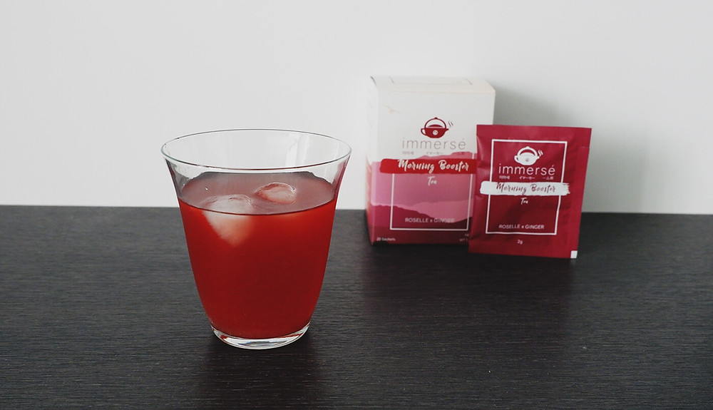 A cup of Cold Serve Lemonade Roselle and Ginger Tea on the foreground, a box and a sachet of morning booster tea in the background
