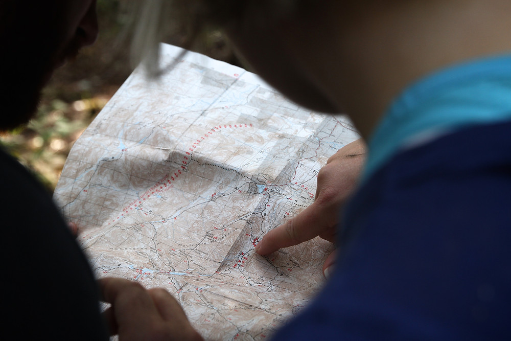 a map with a human finger point down to it