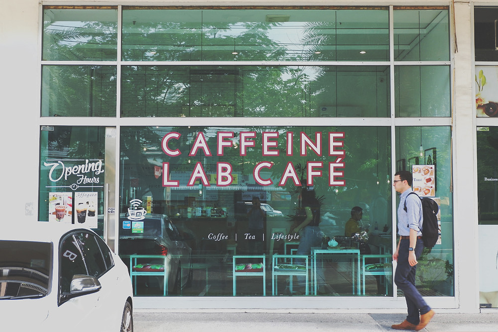 Caffeine Lab Cafe 101-1 Store front, a man walk from right to left