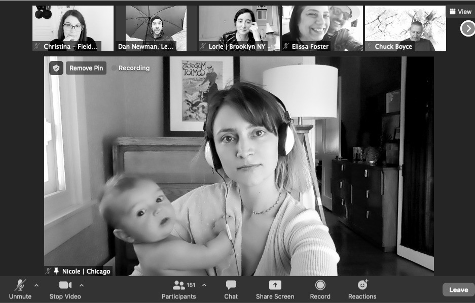 An employee holds a baby while on a Zoom conference call
