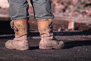 Workmans boots, demolition worker taking