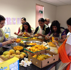 Cutting mangoes for all devotees to enjoy