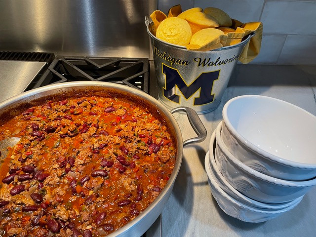 Steaming pot of chili accompanied by cornbread muffins