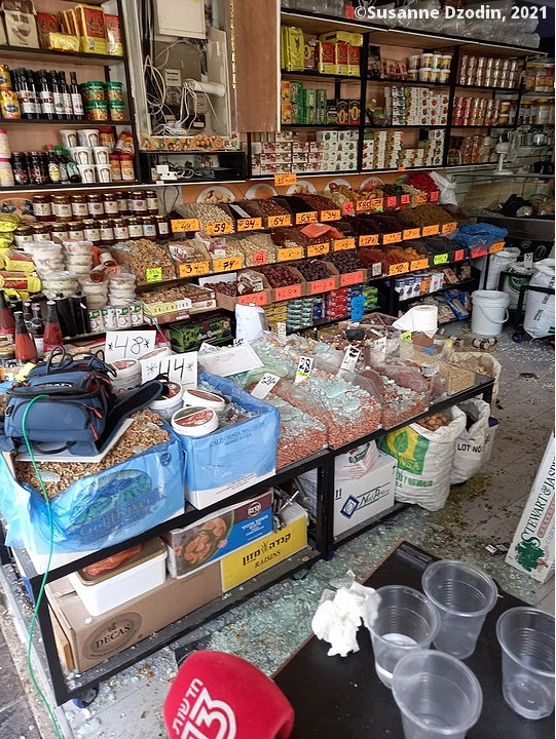 A spice and nut shop near the impact zone with shattered window glass strewn throughout the store.
