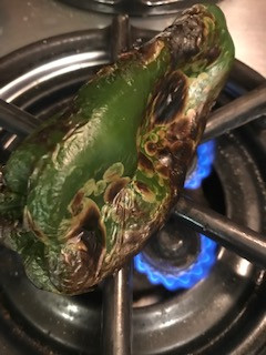 Char poblano pepper over an open flame