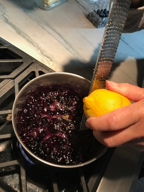 Zesting lemon into the thickened blueberries