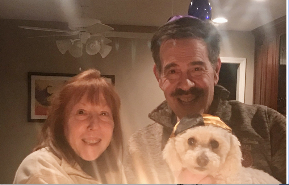 The writer, her husband Neal Alpiner and Buddy the Bichon lighting the Hannukah candles