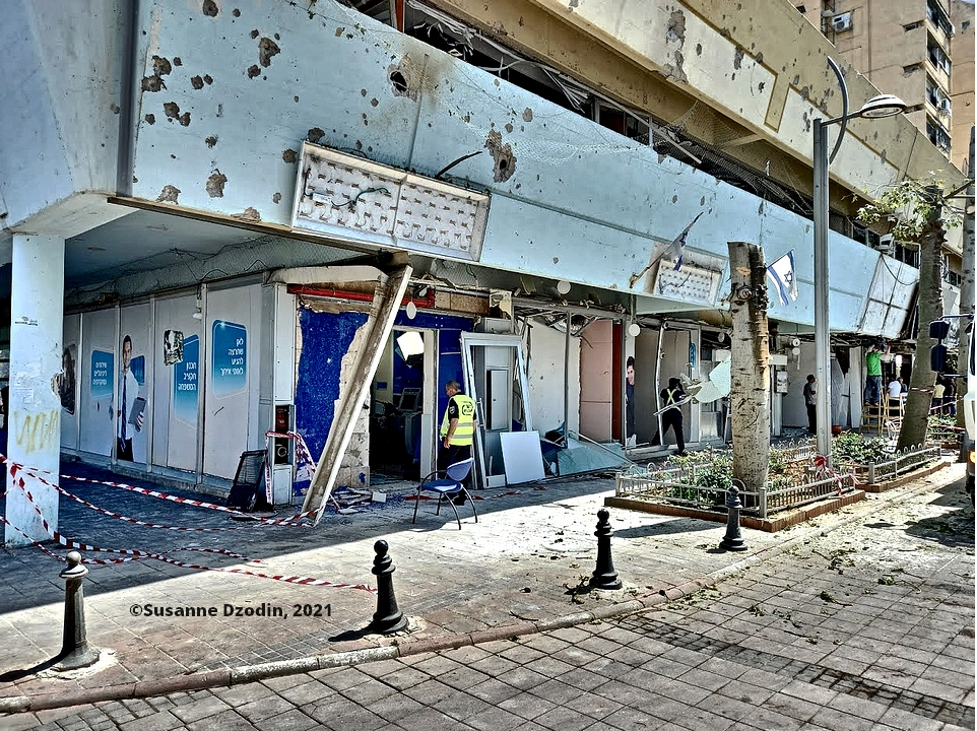 Holon: View of area where a Hamas rocket scored a direct hit on a bus, showing damage to adjacent shops