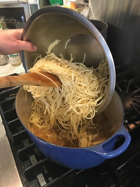 Adding the cooked spaghetti to the pan