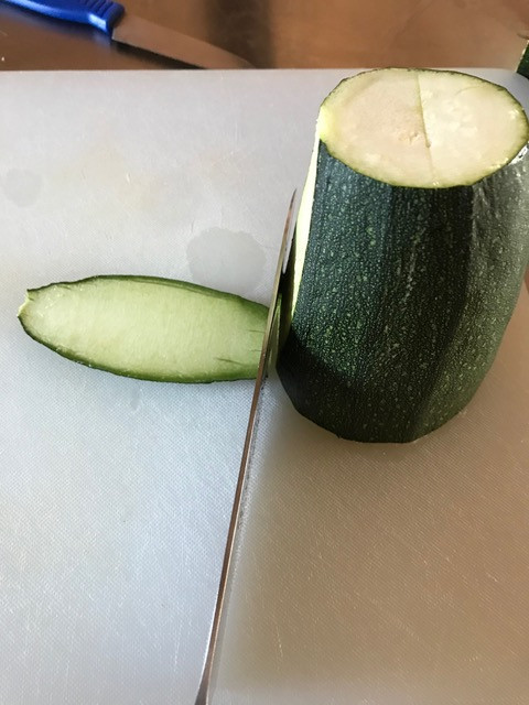 Shave a slice of zucchini off the side so the boat does not rock