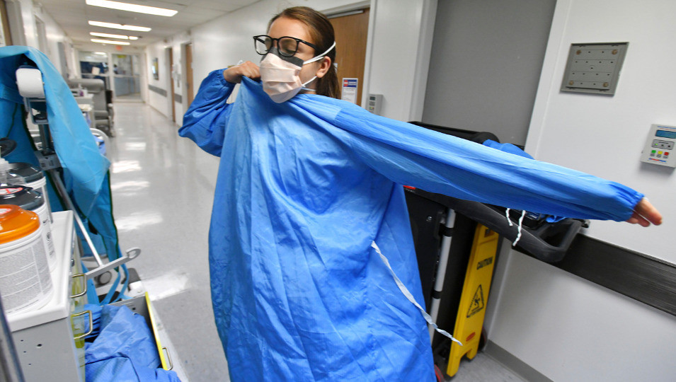 A nurse dons protective garb in a Jacksonville. Fla hospital's Covid ward. Death rates are rising fast.