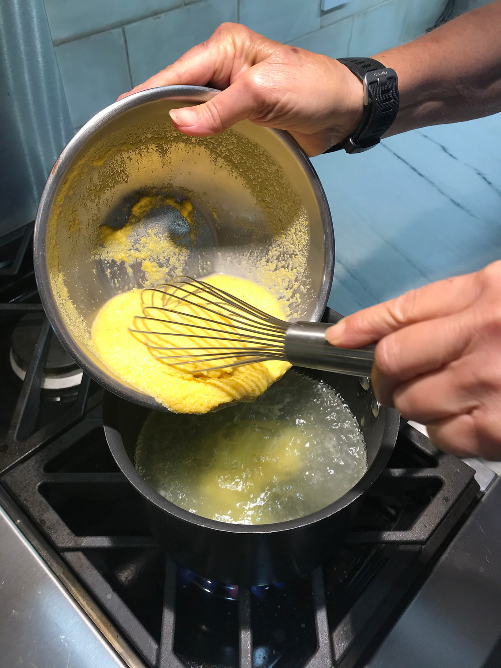 Whisking the moistened polenta into boiling water