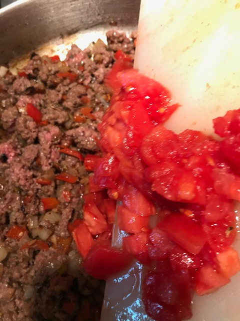 Add the chopped tomatoes to the browned meat and vegetables