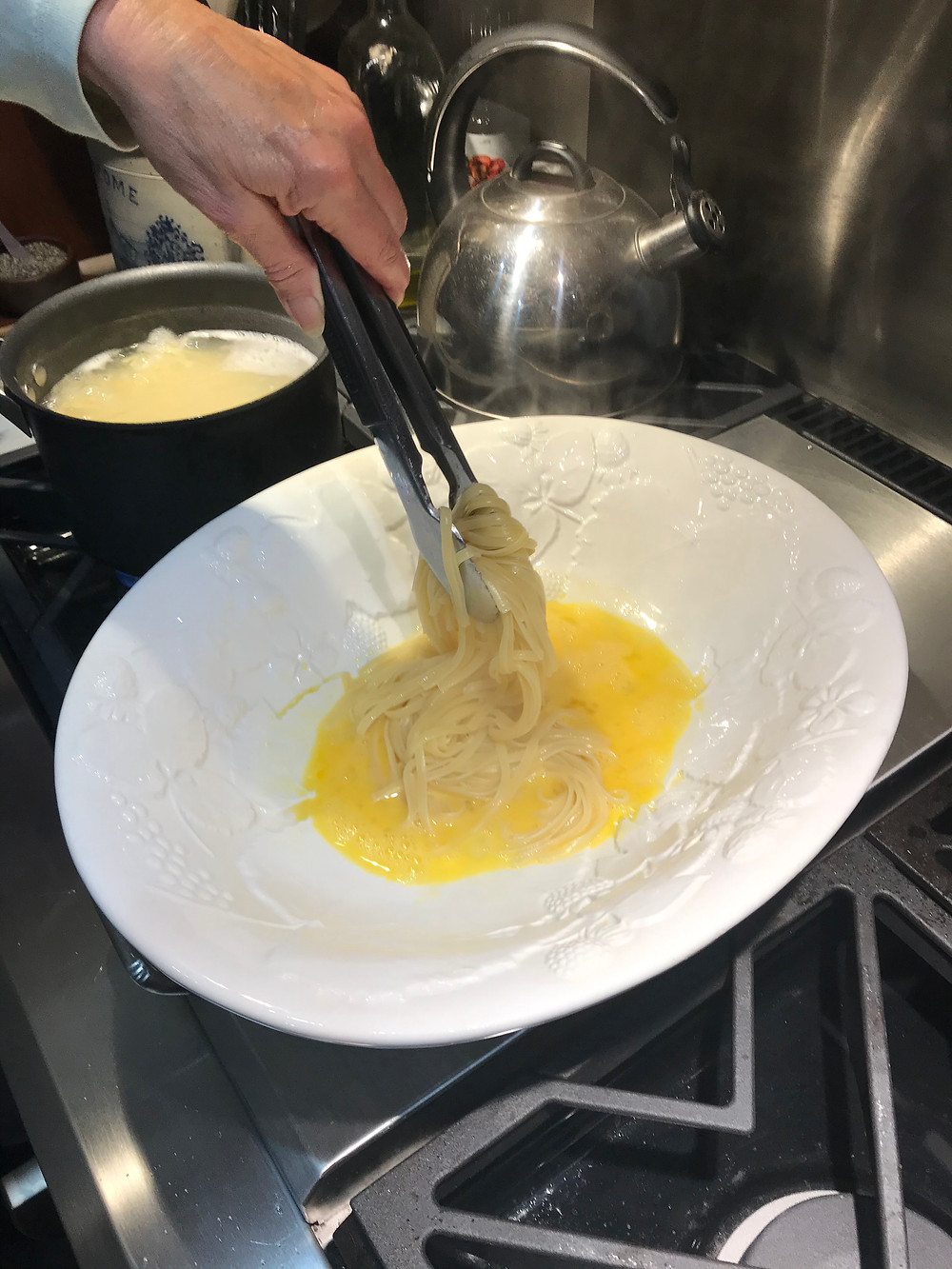 2) Add hot pasta to beaten eggs