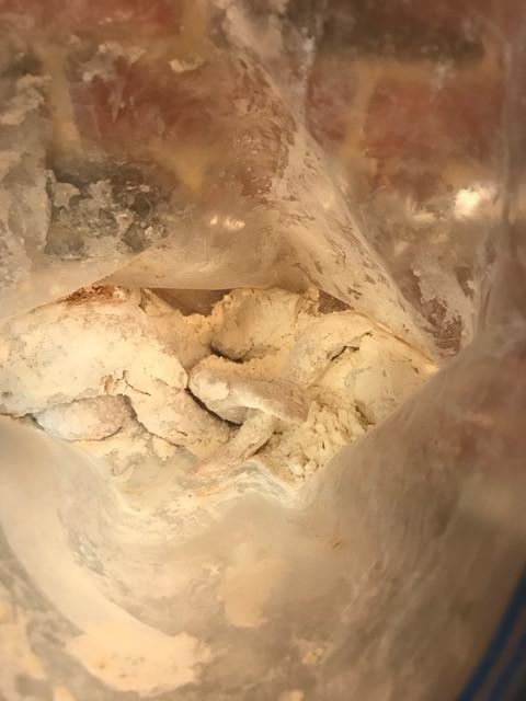 Toss chicken in flour in Ziplock bag