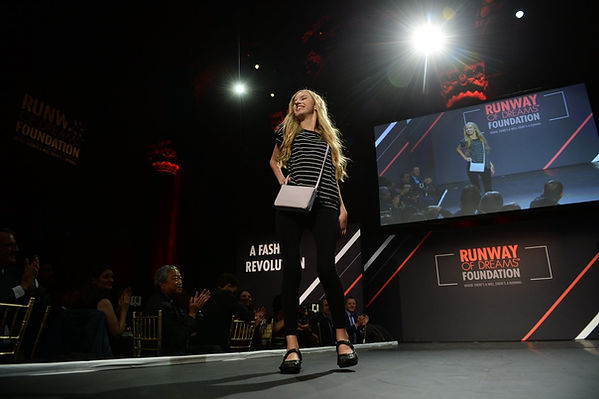 Sarah Todd, a young, blonde, white woman, is walking the runway. Her right hand is on her hip.