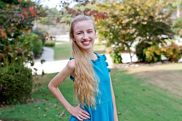 Sarah Todd, a young, blonde, white woman wearing a light blue dress, is smiling at the camera.
