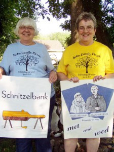 Marge (left) is holding a poster that says Schnitzelbank. It is a tradition to sing the Schnitzelbank song at the annual reunion. The song involves posters with German words on them. Linda (right) has a poster with images of Ottlie and Fredrick Kobs and the date of their wedding. The annual picnic was started by their seven children after Ottilie died. Photo by Jan King