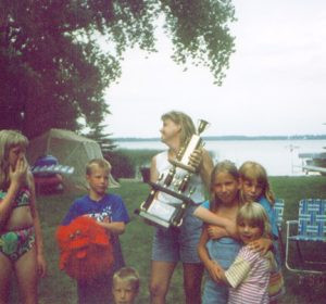 Colleen Lanes, of Alexandria, hoisted the trophy in 1995, surrounded by a group of children.