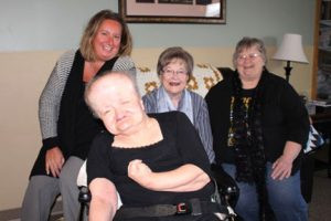 Lutheran Social Services client, Patty, front, shares a laugh in her residence in Mankato with, from left, Shannon Butler, Guardianship Options supervisor; Sandy Birkholz, friendly volunteer visitor and Sally Brigance, volunteer coordinator, Guardianship Options.