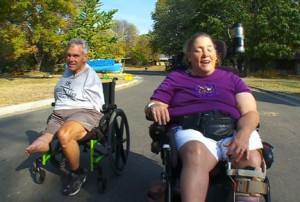 Paul and Maureen Pranghofer take a cruise in their wheelchairs along a street near their home in Golden Valley, where they lead busy lives despite serious physical shortcomings. Photo printed with permission of WCCO-TV