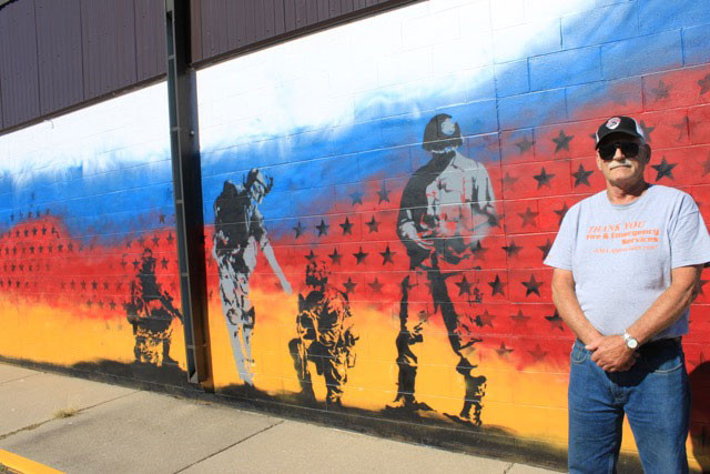 Commander Dave Schulte stands next to Eagle Lake's American Legion intergenerational military mural painted on the exterior wall of its building by artists, veterans and volunteers.