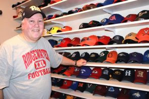 Brad Koenig with more of his hats. He said he isn't actively collecting right now, due to a lack of space. Photo by Steve Palmer