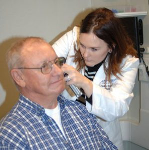 Dr. Holly Eischens examines the ears of Harry Hughes, of Osakis, during a recent appointment. Hughes had been experiencing a gradual hearing loss over the years. Dr. Eischens fitted Hughes with a new pair of hearing aids, and he is now hearing far better than he has in many years. Photo by Jim Palmer