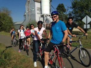 Volunteers took the international students on a bicycle ride last fall. The students are from Congo, Brazil, Japan, China and Malaysia.  John Ebert is the community volunteer pictured. Jordie's Trail Side Café provided treats and beverages to all riders, and the Little Falls Bike Shop provided a tandem bike for students who had never ridden a bike. Photo by Lois Hokanson