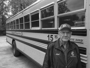 Lloyd Burger next to one of the buses used at Long Prairie Schools. Burger retired after driving a bus route for 50 years. Photo by Jason Brown, Long Prairie Leader