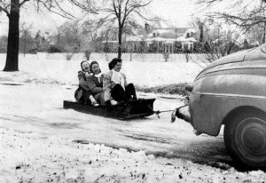 Mardy Grussing photo of the girls riding on a toboggan behind a car in 1947.