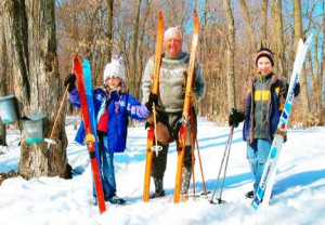 John Kroll, 88, of Long Prairie, and his great-grandchildren, Brennan and Margaret Murtha, skiing together through maple trees, with maple sap buckets hanging on the trees. Contributed photo