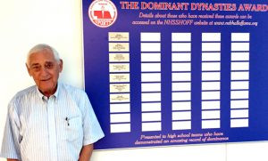 Gene Bjorklun stands in front of Nebraska High School's Sports Hall of Fame Dominant Dynasties Award Board, which shows that his town of Minden, and the basketball teams he played on, won the state's first award. Contributed photo