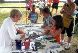 Alison Arngrim (blonde hair with white sweater), who played Nellie Oleson signs autographs at a previous event in Walnut Grove.