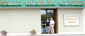 "Greg and Connie Wales in front of the Alexandria Wales Hearing Center. Also pictured is a painting that hangs in the office that sums up the Wales philosophy,  ""Put Your Heart Into It.""   Contributed photo"
