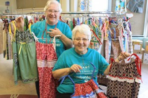 Mary Warner, left, and Annette Perry, right, lead the New Ulm Little Dresses Project that has sent 7,500 dresses to needy children to countries in Africa and other destinations around the world since 2011. Contributed photo