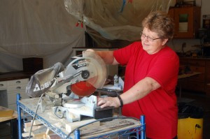 Deb Thorpe using a mitre saw in the shop. Photo by Scott Thoma