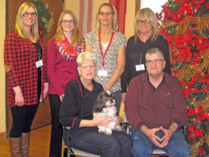 Dusty sits with his masters, Dianne and Roger Seefeld. In back are staff members of the Johnson Memorial Care Center include  Amanda Baird, Colleen Nelson, ​Saige (visitor) and Gail Ochsendorf.  Photo by Ida Kesteloot