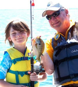 Let's Go Fishing founder Joe Holm gets in a photo with a boy on a recent boat cruise. Contributed photo