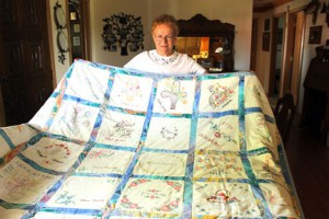 Rita Stracek holds the historic quilt with names of members of the Riverside Ladies Aid from 1938. Photo by Nancy Leasman