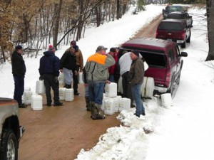 A group of guys from Belle Plaine come together each year to tap and collect sap, and then make maple syrup. Above, they carry buckets of sap from the woodlands to the processing area. Contributed photo
