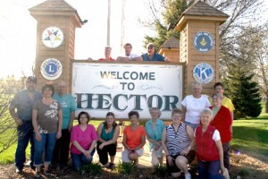 The Hector Minnesota 135th Celebration committee has 20 members organizing all the events during Corn Chaff Days. On top of the sign from the left is Roger Newman, Jeff Heerdt and Al Koenig. On the bottom is Robert Lange, Nancy Fosland, Ken Anderson, Cathy Lee, Stephanie Whalen, Kathy Johnson, Joyce Olinger, Amy Hollan, Marie Walls (kneeling), Lynnette Clark, LeAnn Chapa (red sweater), and Sharon Stark. Not pictured is Judi Lange, Cindy Christopherson, Cyndi Washburn, Vicki Novotny and Barbara Hoyhtya.