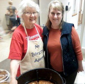 Geneva Stoesz (left) wears her special borscht apron and poses with Karen Flaten in front of a canner of borscht.  Taken by Josh Stoesz