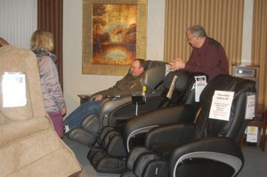 Kevin assists a customer who is trying out a massage chair.  Photo by Scott Thoma