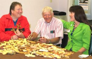 Pam Witte and Lee Eisenschenck, CMWA members, pose with 169 comfort crosses and a Centra Care representative. The group meets monthly at the Whitney Senior Center in St. Cloud. Contributed photo