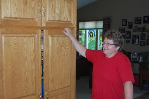 Deb Thorpe showing the kitchen cabinets in her home that she and her late husband, Duane, made together. Note the stained glass projects in the window behind her that Duane made while he battled cancer. Photo by Scott Thoma