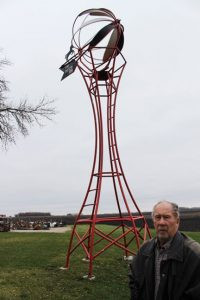 Walter Lehrke stands next to the 32-foot-tall windmill he built and erected on his farm site as a memorial to his late wife, Darlyne.  Her name is written on the tail of the windmill. Photo by Steve Palmer