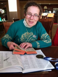 Ursula Hanneliese Tillberg Robinson always has her dictionary with her and always wears a pin: I (heart) Jesus. She is pictured here before starting her night shift at Alexandria's Hampton Inn and Suites. Also shown, her poet merit award and the book her work is published in. Photo by Rachel Barduson